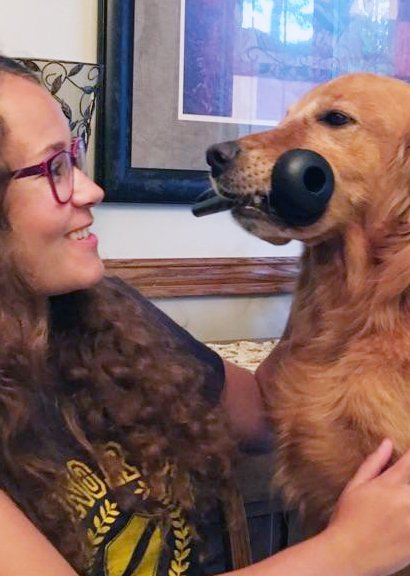 Sidebar photo of Golden Retriever sitting on girl's lap with toy